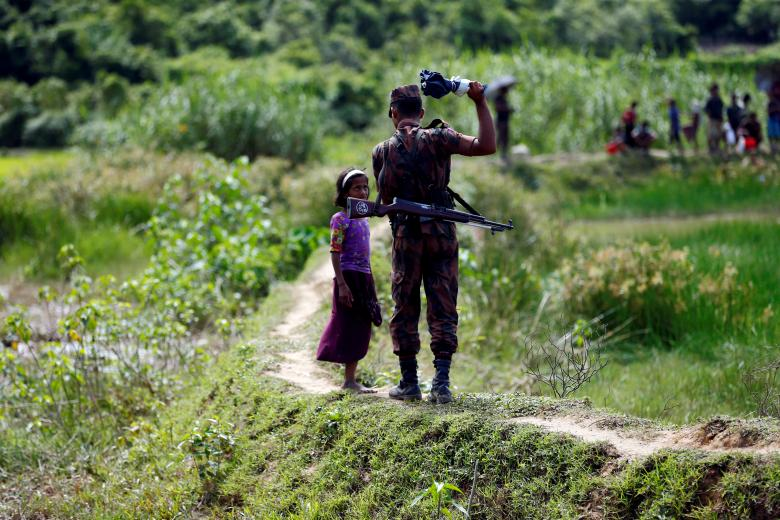 A member of Border Guard Bangladesh (BGB) tells a Rohingya girl not to come on Bangladesh side, in Cox's Bazar