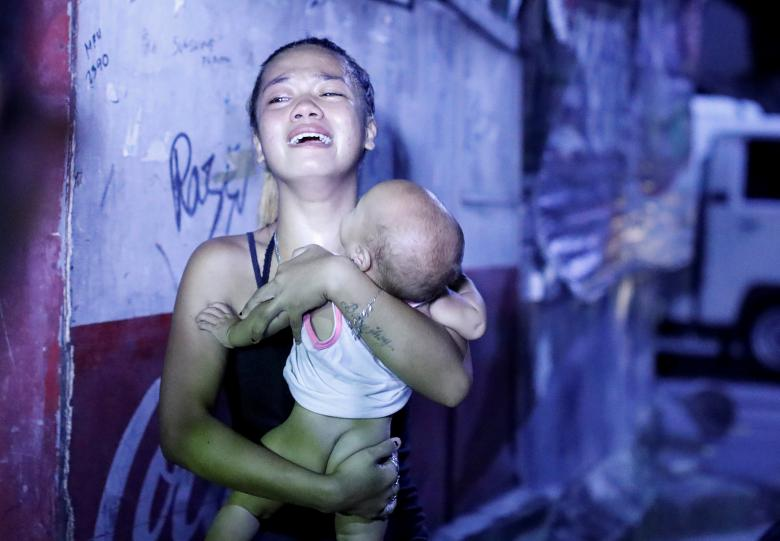A woman cries as she carries her baby after her husband was among those killed during anti-drug operations in Caloocan city, Metro Manila