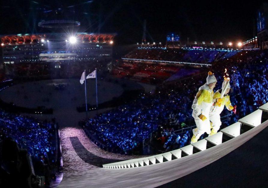 Image forte du début des JO 2018 : deux athlètes nord et sud-coréennes gravissent les marches de la vasque. | Crédit photo AFP